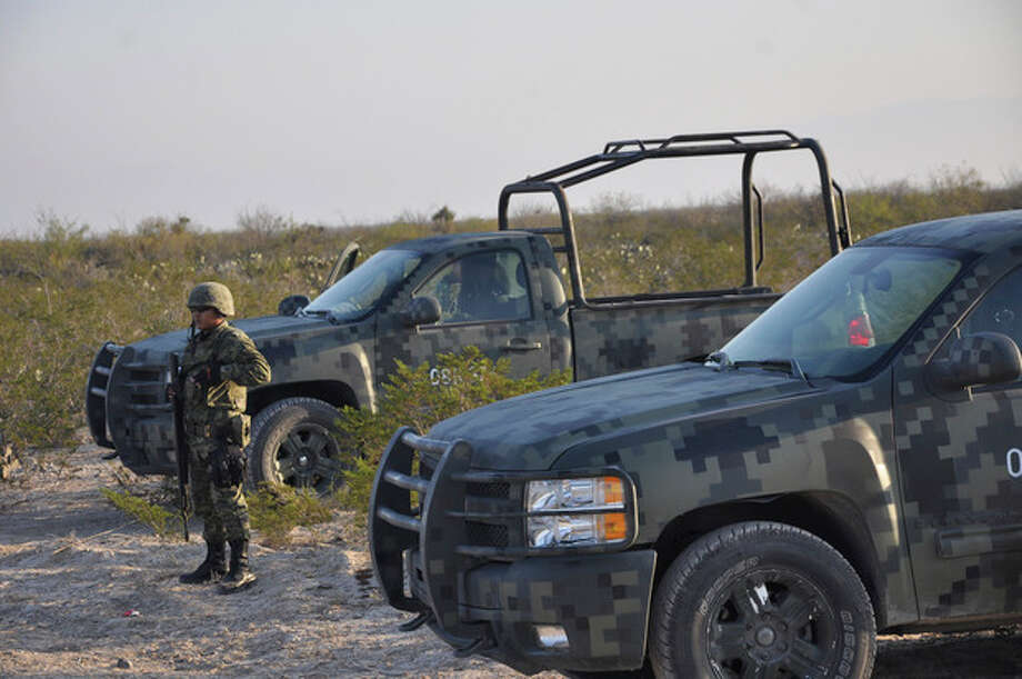 CORRECTS BYLINE TYPO TO VAZQUEZ.- An army soldier stands guard on a dirt road leading to a ranch near the town of Mina, in northern Mexico, Monday, Jan. 28, 2013. At least eight bodies were found in a well near this ranch on Sunday near the site where 20 people went missing late last week, including members of a Colombian-style band, according to a state forensic official. Officials could not confirm whether the bodies belonged to 16 members of the band Kombo Kolombia and their crew, who were reported missing late last week after playing a private show in a bar in the neighboring town of Hidalgo north of Monterrey. (AP Photo/Emilio Vazquez) / AP