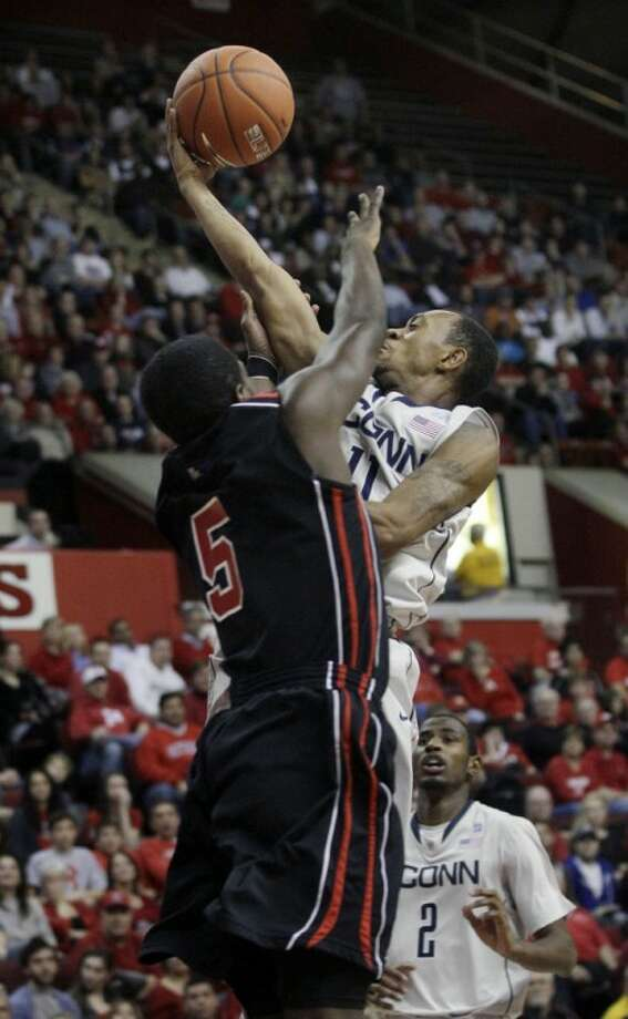 Connecticut's Ryan Boatright (11) takes a shot as Rutgers' Eli Carter (5) tries to block his path during the first half of an NCAA college basketball game in Piscataway, N.J., Saturday, Jan. 7, 2012. (AP Photo/Mel Evans)