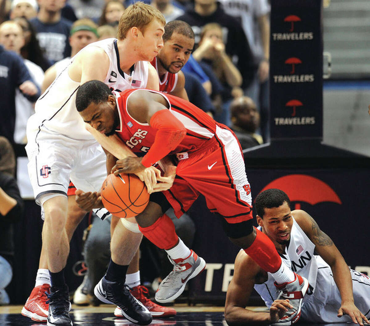 AP photo UConn's Niels Giffey, left, fouls Rutgers' Eli Carter, center, on a play during the first half of Sunday's game. Giffey came off the bench and made a strong contribution to the Huskies' victory. He efforts drew some post-game comparisons to the type of all-around game often turned in by Kelly Faris, the versatile standout on the UConn women's squad.