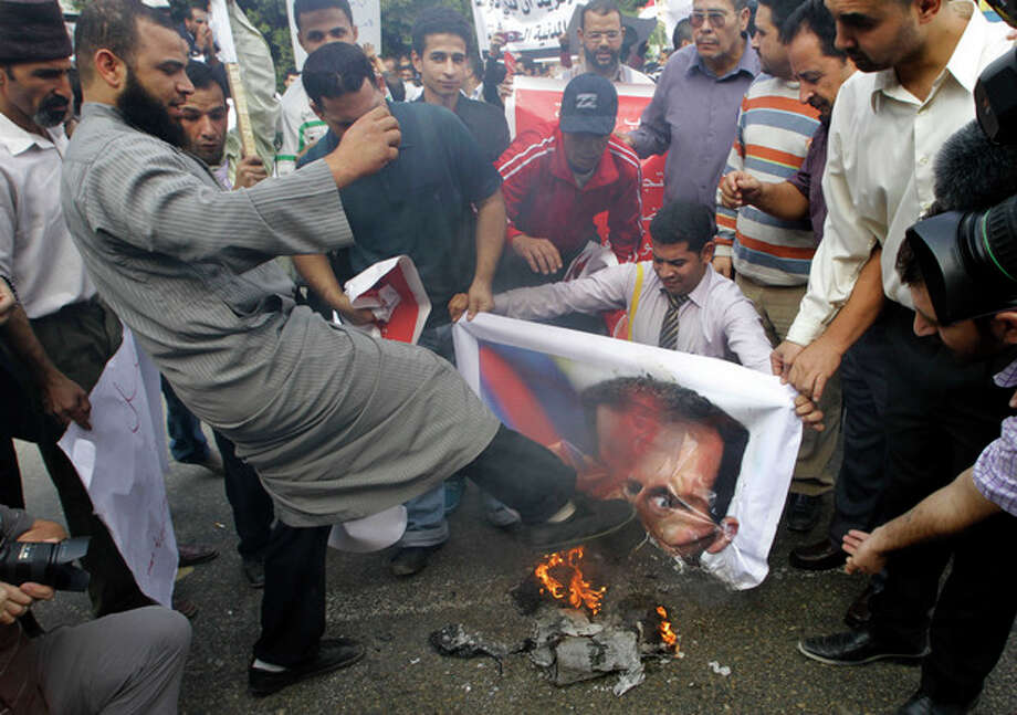 A Syrian protester kicks a burning picture of Syrian President Bashar Assad during a protest in front of the Arab League headquarters in Cairo, Egypt, Saturday, Nov.12, 2011 where an Arab League emergency session on Syria is taking place to discuss the country's failure to end bloodshed caused by government crackdowns on civil protests. Protesters called on the Arab League to suspend the country's membership. (AP Photo/Amr Nabil) / AP