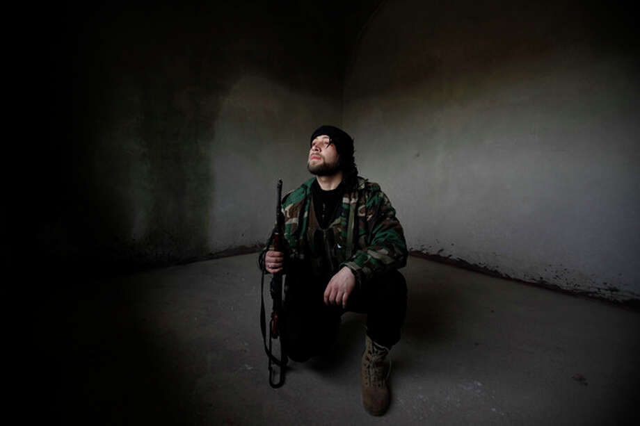 A Syrian rebel looks out after Syrian army tanks enter the northwestern city of Idlib, Syria, Tuesday, Feb. 14, 2012. Syrian government forces renewed their assault on the rebellious city of Homs on Tuesday in what activists described as the heaviest shelling in days, as the U.N. human rights chief raised fears of civil war. (AP Photo) / AP