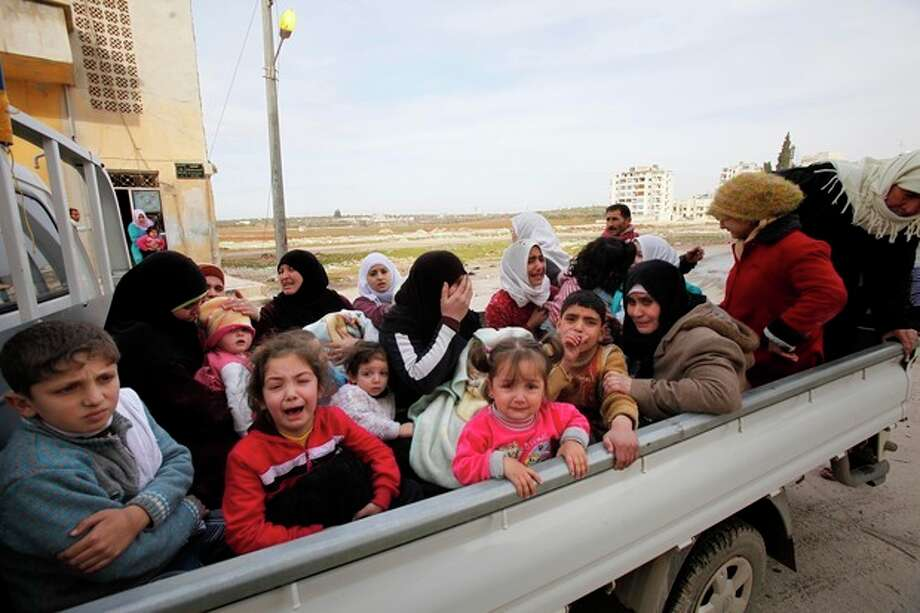 Civilians flee from fighting after Syrian army tanks enter the northwestern city of Idlib, Syria, Tuesday, Feb. 14, 2012. Syrian government forces renewed their assault on the rebellious city of Homs on Tuesday in what activists described as the heaviest shelling in days, as the U.N. human rights chief raised fears of civil war. (AP Photo) / AP