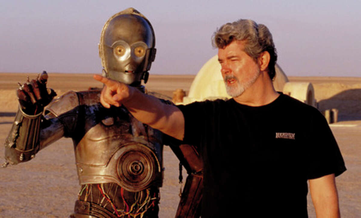 """** FILE ** In this undated publicity photo released by Lucasfilm Ltd. & TM, director George Lucas directs actor Anthony Daniels, who plays the robot C-3PO, in """"Star Wars II: Attack of the Clones,"""" on location in the Tunisian desert. Lucasfilm said in a statement Monday, Jan. 28, 2013, that it's postponing the scheduled fall 3-D releases of ?""""Star Wars: Episode II - Attack Of The Clones?"""" and ?""""Episode III - Revenge of the Sith?"""" to instead focus its efforts on ?""""Star Wars: Episode VII.?"""" (AP Photo/Lucasfilm Ltd. & TM, Lisa Tomasetti, file)"""