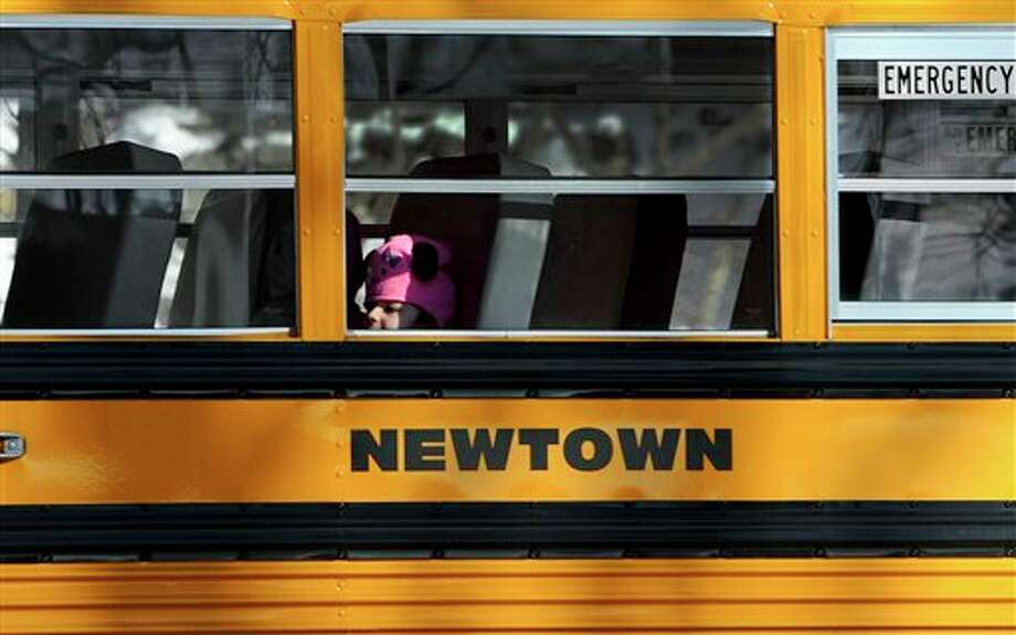 A child sits on a Newtown bus leaving the new Sandy Hook Elementary School on the first day of classes in Monroe, Conn., Thursday, Jan. 3, 2013. Classes resumed Thursday for the students of the school where a gunman last month burst in and killed 20 children and six adults before killing himself. It was the second largest school shooting in the U.S. history. With their school still being treated as a crime scene, the more than 400 students of Sandy Hook Elementary School attended classes at the neighboring town's Chalk School. AP Photo/Jessica Hill) / A2013