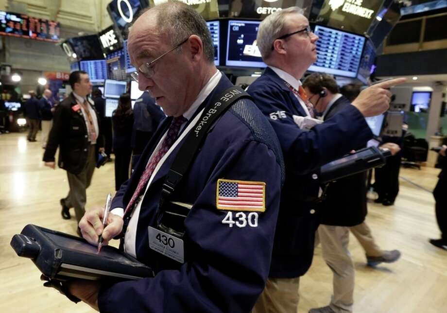Traders Frederick Reimer, left, and David O'Day, right, work on the floor of the New York Stock Exchange Wednesday, Jan. 30, 2013. Stocks are falling after the government revealed that economic growth shrank in the final quarter of 2012. (AP Photo/Richard Drew) / AP