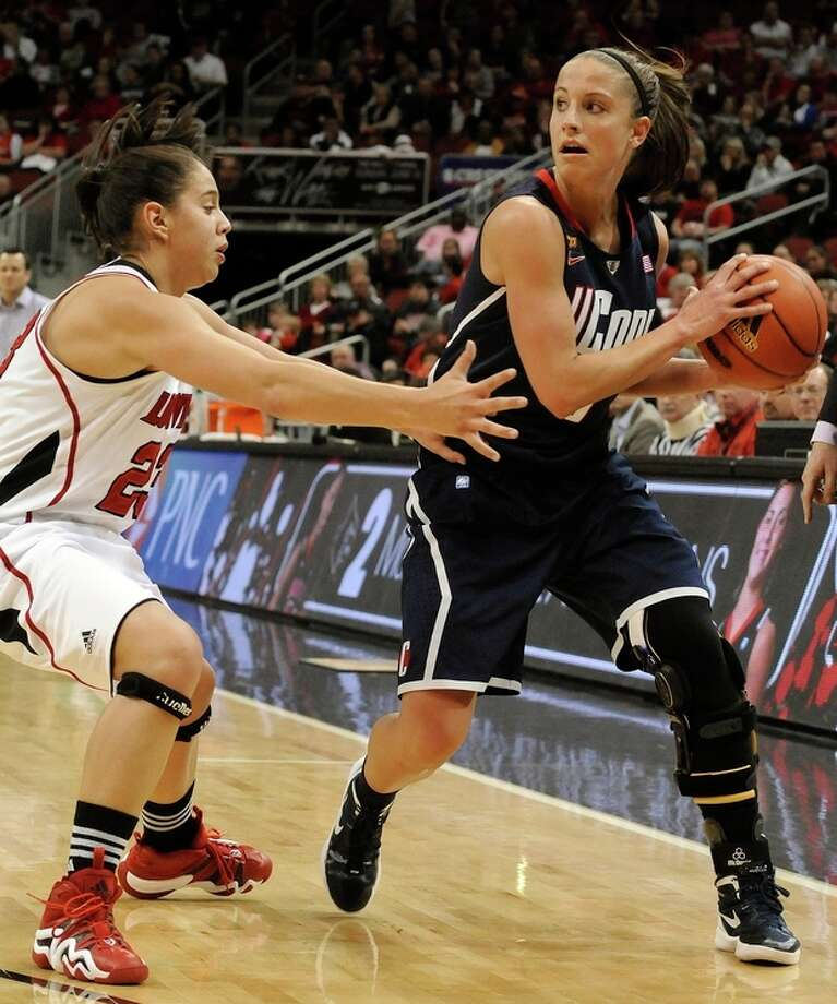 Connecticut's Caroline Doty, right, looks for an opening around Louisville's Shoni Schimmel during the second half of their NCAA college basketball game Tuesday, Feb. 7, 2012 in Louisville, Ky. Connecticut defeated Louisville 56-46. (AP Photo/Timothy D. Easley) / Timothy D. Easley