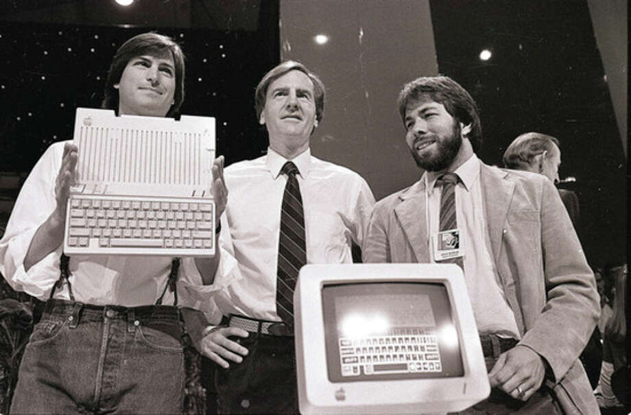 FILE - In this April 24, 1984, file photo, from left, Steve Jobs, chairman of Apple Computers, John Sculley, president and CEO, and Steve Wozniak, co-founder of Apple, unveil the new Apple IIc computer in San Francisco. Apple on Wednesday, Oct. 5, 2011 said Jobs has died. He was 56. (AP Photo/Sal Veder, File) / AP1984
