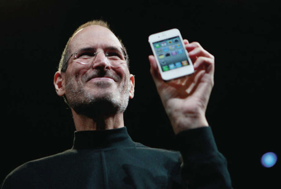 FILE - In this June 7, 2010, file photo, Apple CEO Steve Jobs holds a new iPhone at the Apple Worldwide Developers Conference in San Francisco. Apple on Wednesday, Oct. 5, 2011 said Jobs has died. He was 56. (AP Photo/Paul Sakuma, File) / AP2010