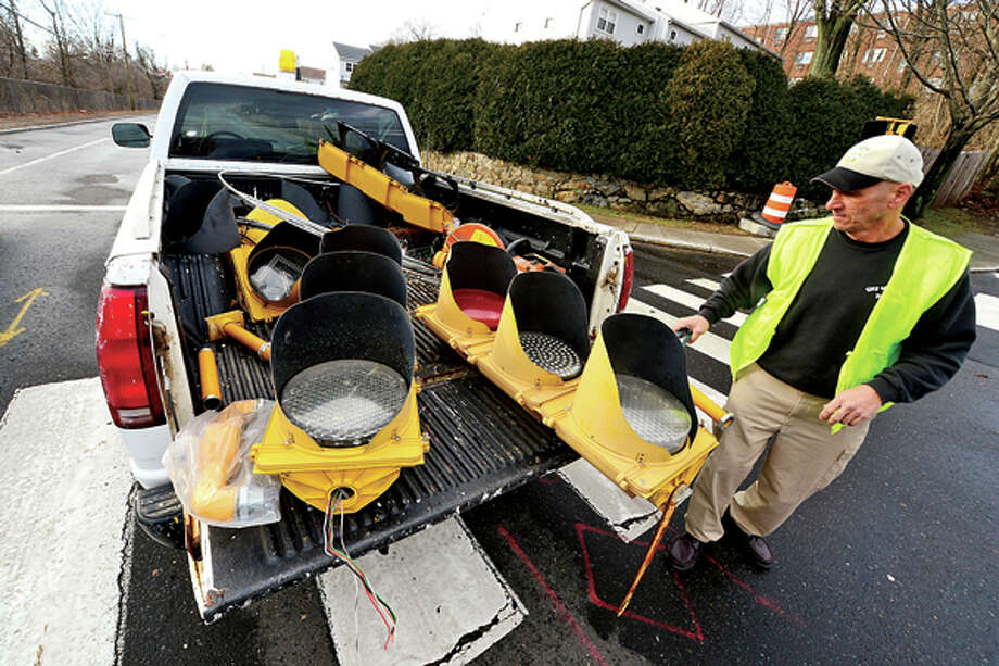 DPW Traffic Supervisor Bob Atunes removes a signal light that came down in the storm on CT Ave. Heavy winds associated with a storm that effected the area early Thursday morning brought down wires and trees throughout Norwalk. Hour photo / Erik Trautmann / (C)2012, The Hour Newspapers, all rights reserved