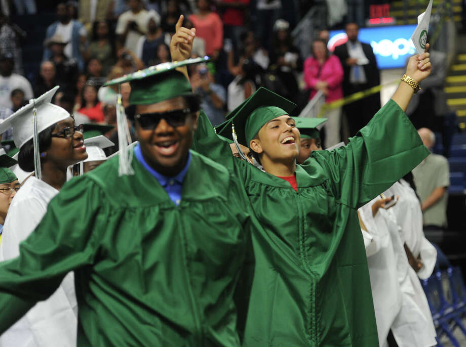Grads Yarrell Battle, left, and Raymond Benson celebrate during the Bassick High School graduation at the Webster Bank Arena in Bridgeport, Conn. on Tuesday, June 14, 2016. Photo: Brian A. Pounds, Hearst Connecticut Media / Connecticut Post