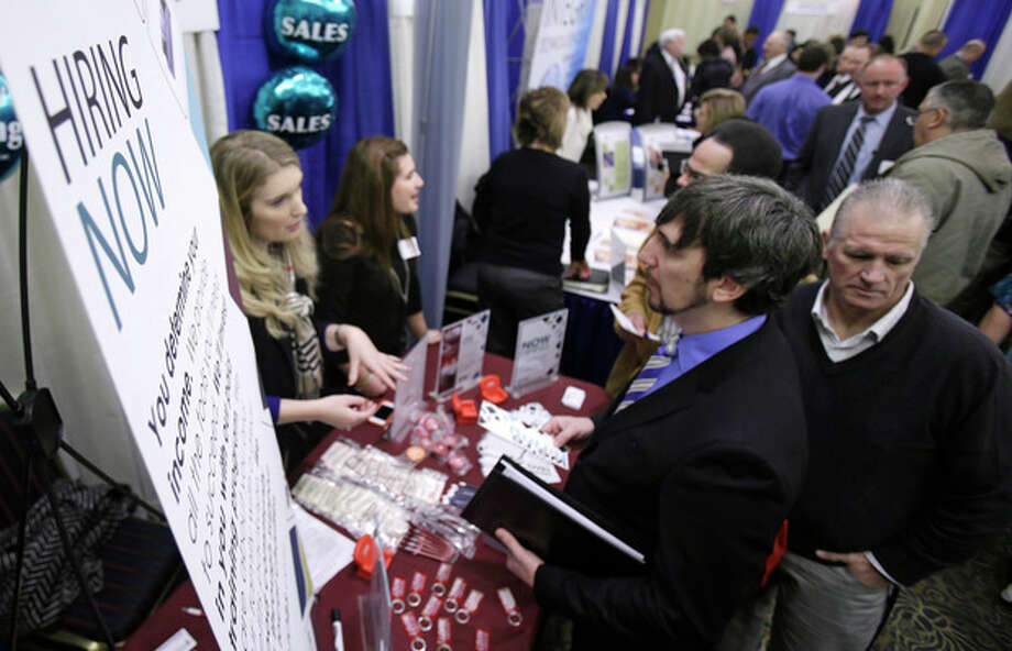 In this Wednesday, Jan. 16, 2013, photo, perspective job seekers talk with employers during a job fair in Cuyahoga Falls, Ohio. The number of Americans seeking unemployment aid jumped last week, though the increase mostly reflected difficulties the government has seasonally adjusting its numbers. Applications are still at levels signaling modest hiring. (AP Photo/Tony Dejak) / AP