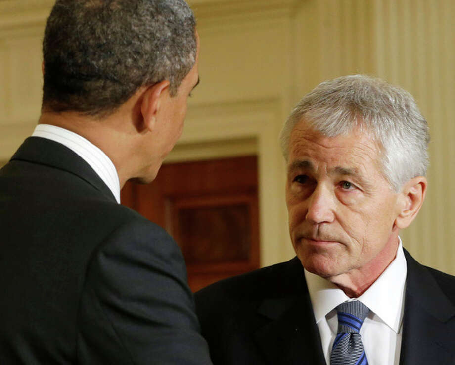 FILE - In this Jan. 7, 2013 file photo, President Barack Obama shakes hands with Defense Secretary-nominee, former Nebraska Sen. Chuck Hagel, in the East Room of the White House in Washington. Hagel says his months fighting in Vietnam alongside his brother Tom shaped his view of what it's like to be a soldier in war, an experience that will inform his work if the Senate confirms him to be defense secretary. While Hagel, who was twice wounded, suggests caution when using military force, he also adopts a hard line toward Iran. His nomination hearings begin Thursday. (AP Photo/Pablo Martinez Monsivais. File) / AP