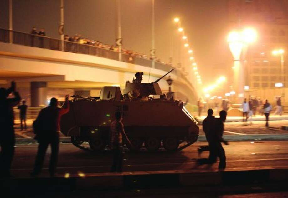 Anti-government protesters run around an Egyptian army armoured personnel carrier, near the Tahrir Square, in downtown Cairo, Egypt, Friday, Jan. 28, 2011. Egyptian activists protested for a fourth day as social networking sites called for a mass rally in the capital Cairo after Friday prayers, keeping up the momentum of the country''s largest anti-government protests in years. (AP Photo/Lefteris Pitarakis)