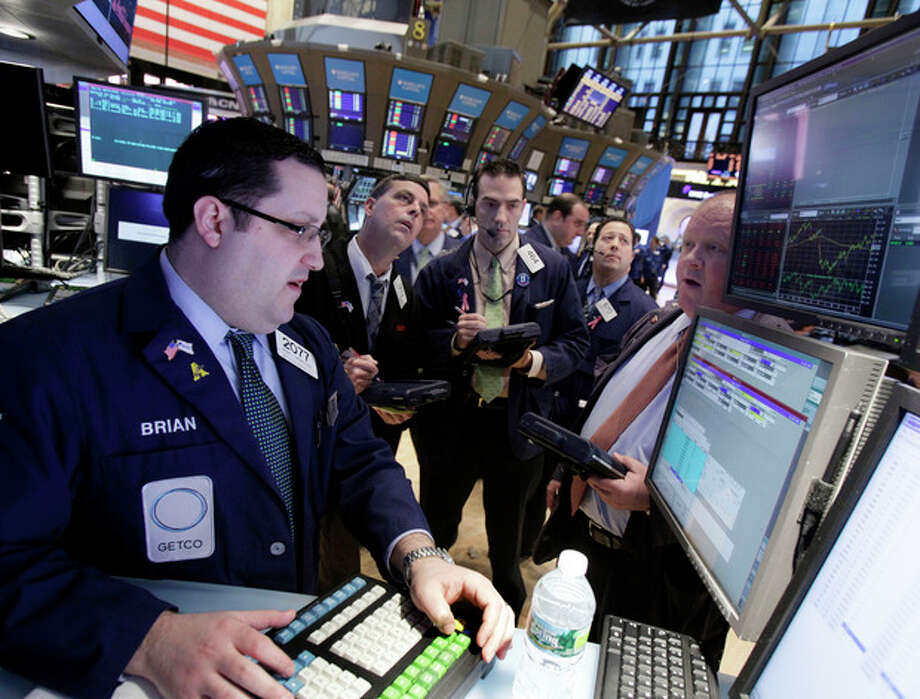 Traders gather at the post of specialist Brian Fairbrother, left, on the floor of the New York Stock Exchange Monday, Feb. 27, 2012. U.S. stocks pulled back Monday from some of their highest levels in three and a half years. (AP Photo/Richard Drew) / AP