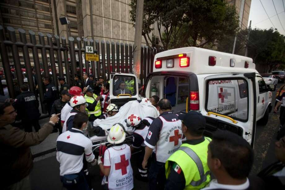 An injured person is carried into an ambulance after an explosion at an adjacent building to the executive tower of Mexico's state-owned oil company PEMEX, in Mexico City, Thursday Jan. 31, 2013. An explosion at the main headquarters of Mexico's state-owned oil company in the capital killed more than 10 people and injured some 80 as it heavily damaged three floors of the building, sending hundreds into the streets and a large plume of smoke over the skyline. (AP Photo/Eduardo Verdugo)
