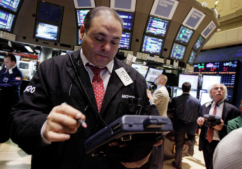 In this Feb. 3, 2012 photo, trader Anthony Riccio, left, works on the floor of the New York Stock Exchange. Stocks were trading lower on Tuesday, Feb. 7,2012, as talks dragged on in Greece to agree the terms of a second bailout _ and avoid looming bankruptcy _ despite intense pressure from the country's euro partners. (AP Photo/Richard Drew) / AP