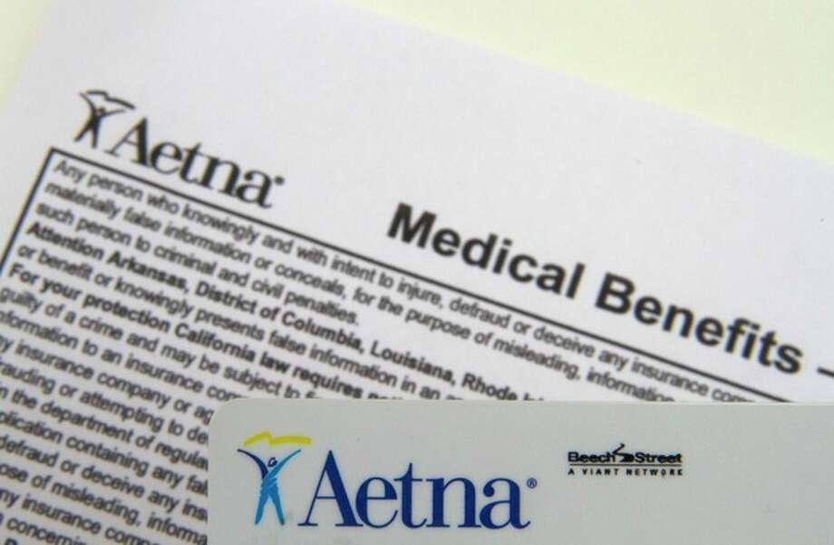 FILE - This Jan. 30, 2012 file photo, shows an Aetna benefits card in Surfside, Fla. Aetna's fourth-quarter earnings sank 49 percent as the health insurer's medical costs climbed and it absorbed costs for litigation and the purchase of another insurer, among other expenses the company announced Thursday Jan. 31, 2013. (AP Photo/Wilfredo Lee, File) / AP