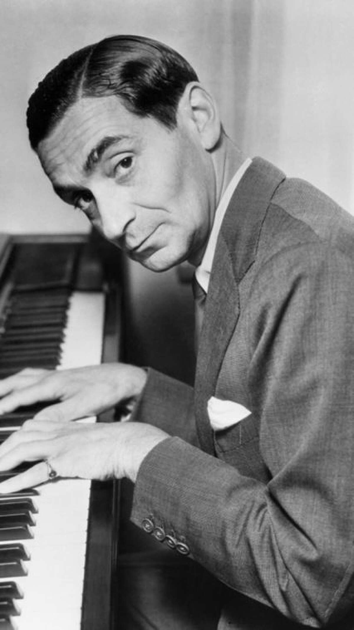 """17 Apr 1935 --- 4/17/35: Irving Berlin, famed composer who has just completed the score for RKO-radio's new musical, """"Top hat,"""" starring Fred Astaire and Ginger Rogers, finds the long lost chord on his piano but doesn't think it will fit a popular song. In fact, he doesn't think, to judge by his expression, it will fit anything. --- Image by © Bettmann/CORBIS"""
