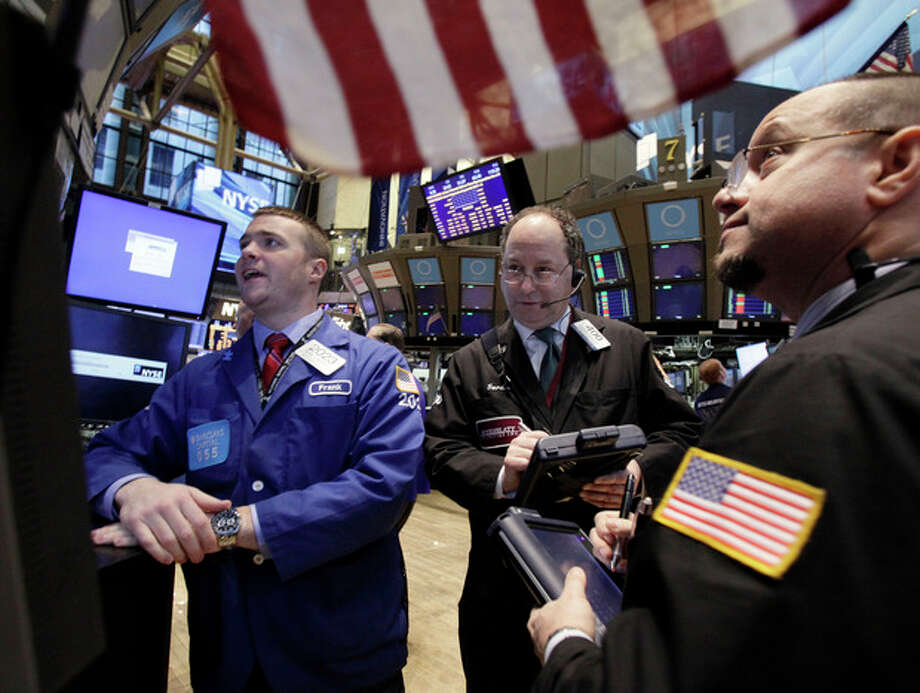 Specialist Frank Masiello, left, works with traders on the floor of the New York Stock Exchange Monday, Feb. 27, 2012. U.S. stocks pulled back Monday from some of their highest levels in three and a half years. (AP Photo/Richard Drew) / AP