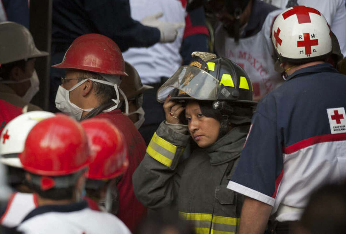 ALTERNATIVE CROP OF MXEV102.- Rescue workers and firefighters gather as emergency responders search for trapped survivors at the site on an explosion in a building at Mexico's state-owned oil company PEMEX complex, in Mexico City, Thursday Jan. 31, 2013. The explosion killed more than 10 people and injured some 80 as it heavily damaged three floors of the building. According to civil protection and local media some people remained trapped in the debris from the explosion, which occurred in the basement of an administrative building next to the iconic, 52-story tower of Petroleos Mexicanos, or PEMEX.(AP Photo/Eduardo Verdugo)