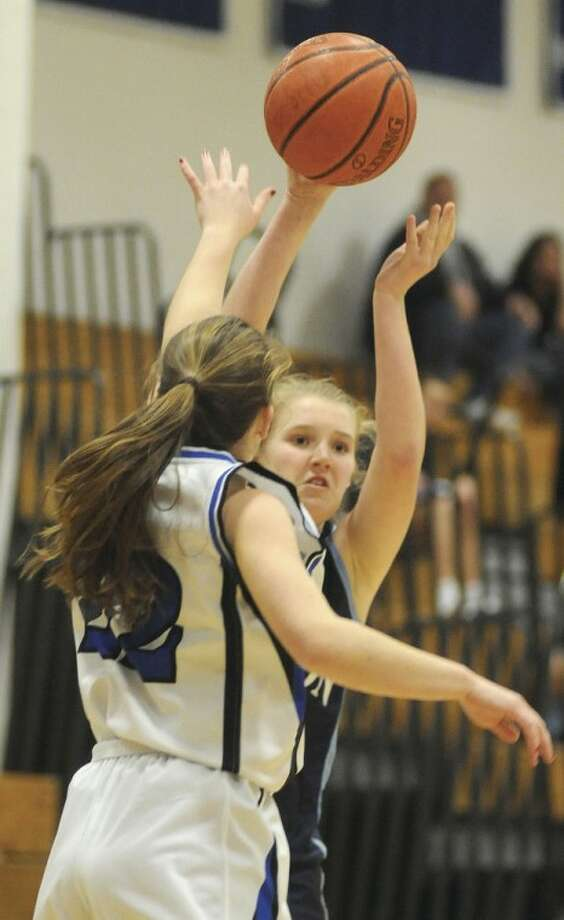 Hour photo/John Nash Wilton's Erin Cunningham, rear, looks to pass into the post as Darien's Susan Biggart defends during Tuesday's game.
