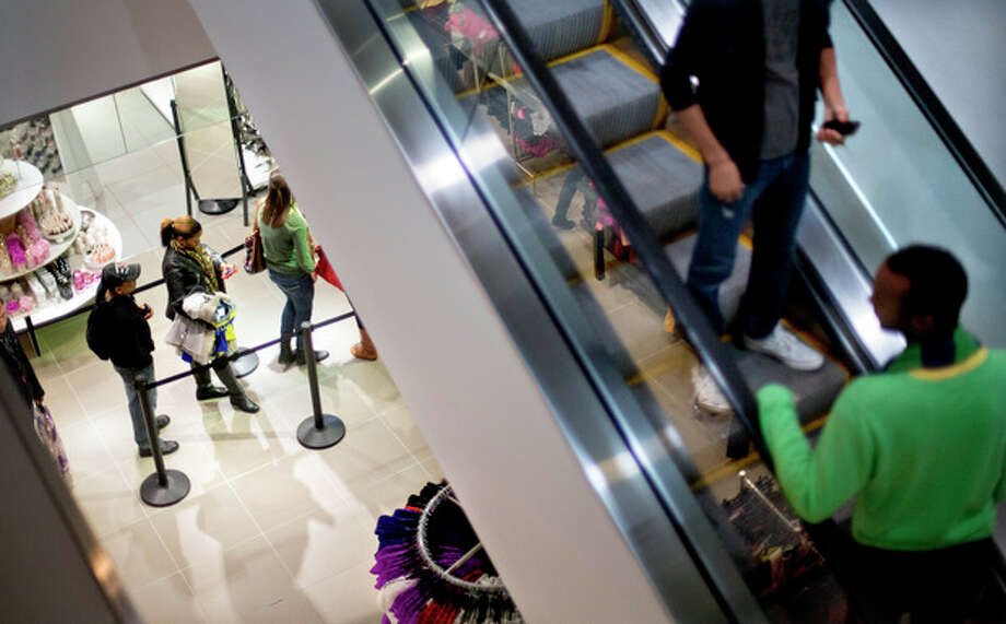 In this Wednesday, Dec. 12, 2012, photo, shoppers wait on line at the checkout counter to purchase goods at an H&M store, in Atlanta. U. S. consumers increased their spending in December at a slower pace, while their income grew by the largest amount in eight years. Income surged because companies rushed to pay dividends before income taxes increased on high-earners. (AP Photo/David Goldman) / AP