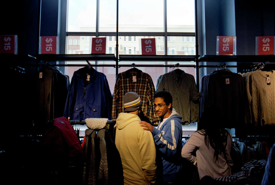 In this Wednesday, Dec. 12, 2012, photo, Chris Ghiathi, right, shops with friend Shawn Patel, left, in an H&M store, in Atlanta. U. S. consumers increased their spending in December at a slower pace, while their income grew by the largest amount in eight years. Income surged because companies rushed to pay dividends before income taxes increased on high-earners. (AP Photo/David Goldman) / AP