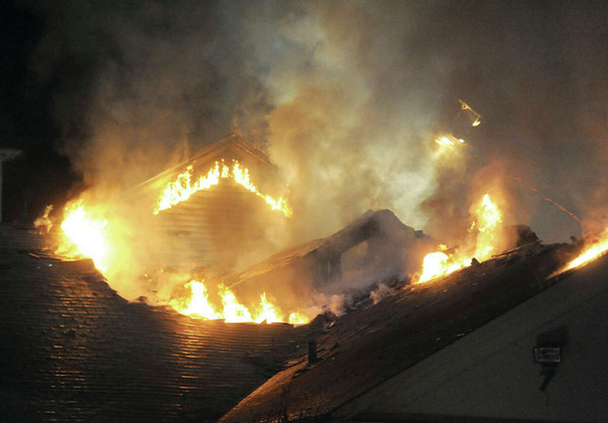 Hour Photo/John Nash - A fire scorches the roof on the rear portion of the Saugatuck Congregational Church on Sunday night.