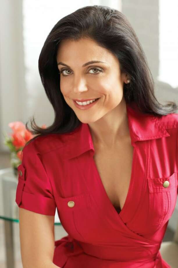Bethenny Frankel in red (cross) dress with brass buttons smiling looking in camera