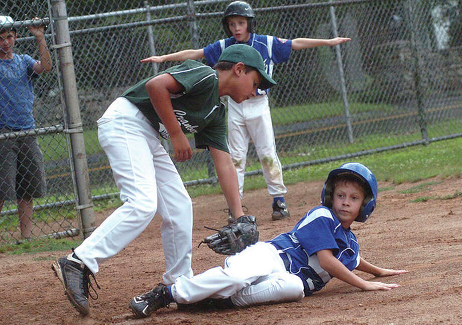 Hour photo/Matthew Vinci Kyle Spezzano of Cal Ripken slides safely into home under the tag of CranburyÕs Chris Cunningham during Tuesday nightÕs opener of the Tom Corbo youth baseball tournament for 9-10-year-old players. The Ripken squad posted a 7-3 victory / (C)2011, The Hour Newspapers, all rights reserved