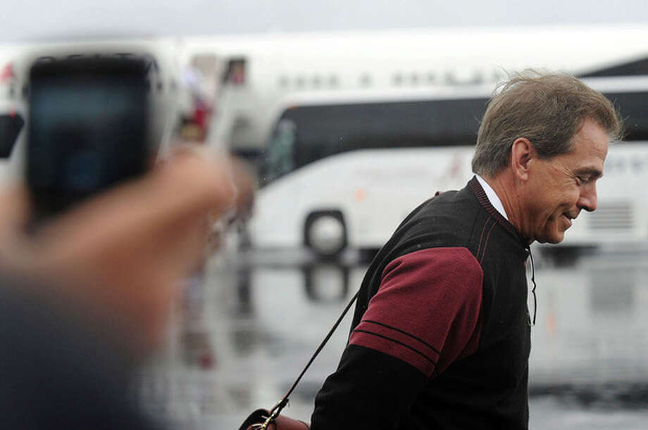 Coach Nick Saban smiles as he heads towards fans, at the Tuscaloosa Regional Airport, after he and the University of Alabama football team returned to Tuscaloosa, Ala., Tuesday, Jan. 10, 2012. Alabama defeated LSU 21-0 for the BCS National Championship title. It's the second national championship title in three years for Alabama. (AP Photo/The Birmingham News, Tamika Moore) / The Birmingham News