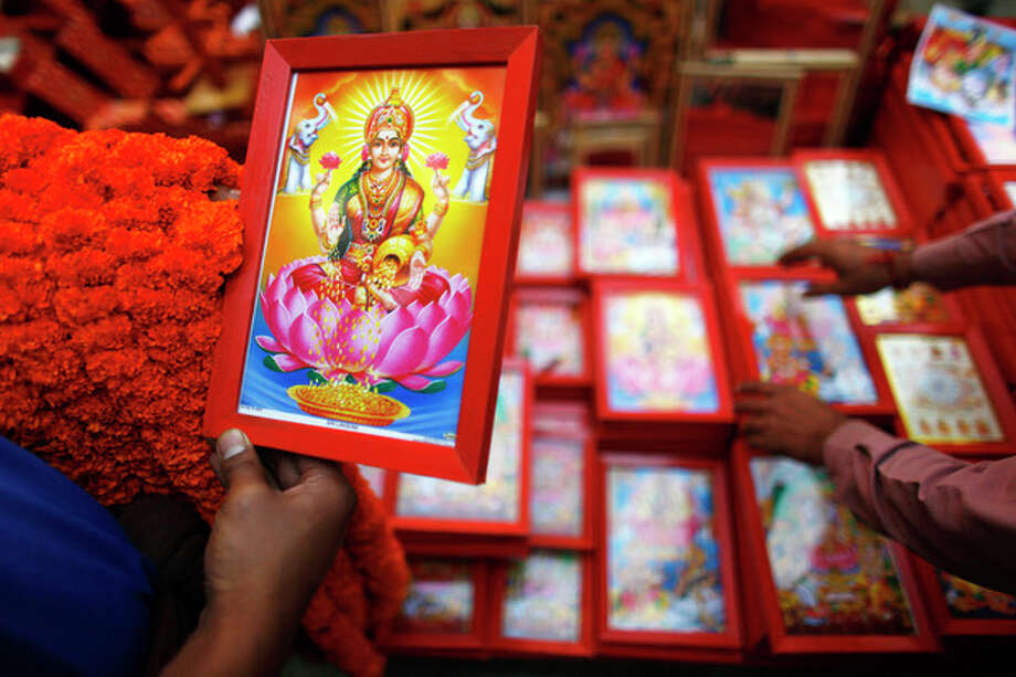 AP Photo/Niranjan Shrestha A Nepalese man selects a picture of Lakshmi, the Hindu goddess of wealth, during the second day of Tihar festival in Katmandu, Nepal, Wednesday. Nepalese are celebrating the five-day long festival of Tihar, dedicated to the worship of various animals, the Goddess Lakshmi and brothers. / AP