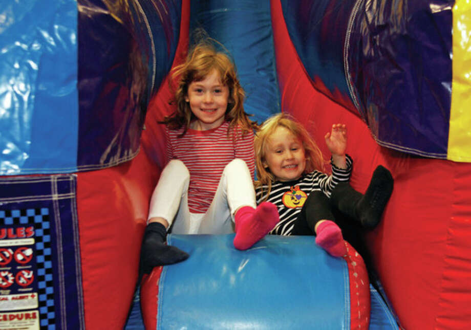 """Sisters Ellie and Lindy Mueller (7 & 5) play on an inflatable slide during Pump It Up's """"Noon Years Eve"""" Party Saturday morning in Norwalk. Hour Photo / Danielle Robinson"""