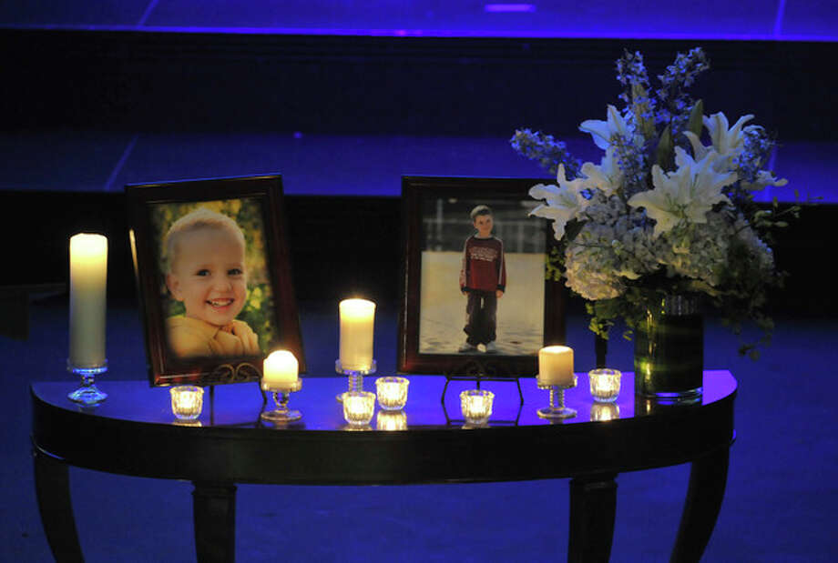 Photos of Charlie, right, and Braden Powell are displayed during their funeral service Saturday, Feb. 11, 2012, in Tacoma, Wash. The boys died Feb. 5, 2012, when their father, Josh Powell, set fire to the home he was living in while they visited. Powell had been a person of interest in the 2009 disappearance of his wife Susan. (AP Photo/The News Tribune, Lui Kit Wong, Pool) / The News Tribune Pool