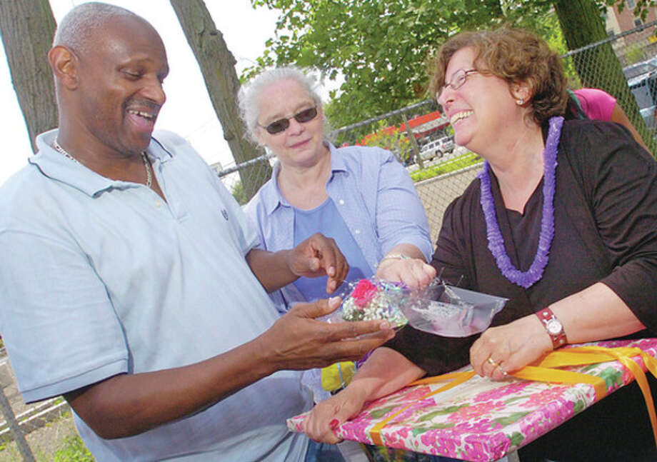 Briggs High School Principal Elaine Lane receives gifts from guidance couselor Bobby Miller as Lynn Ferris looks on during a retirement party for Lane at the school Friday. / (C)2011, The Hour Newspapers, all rights reserved