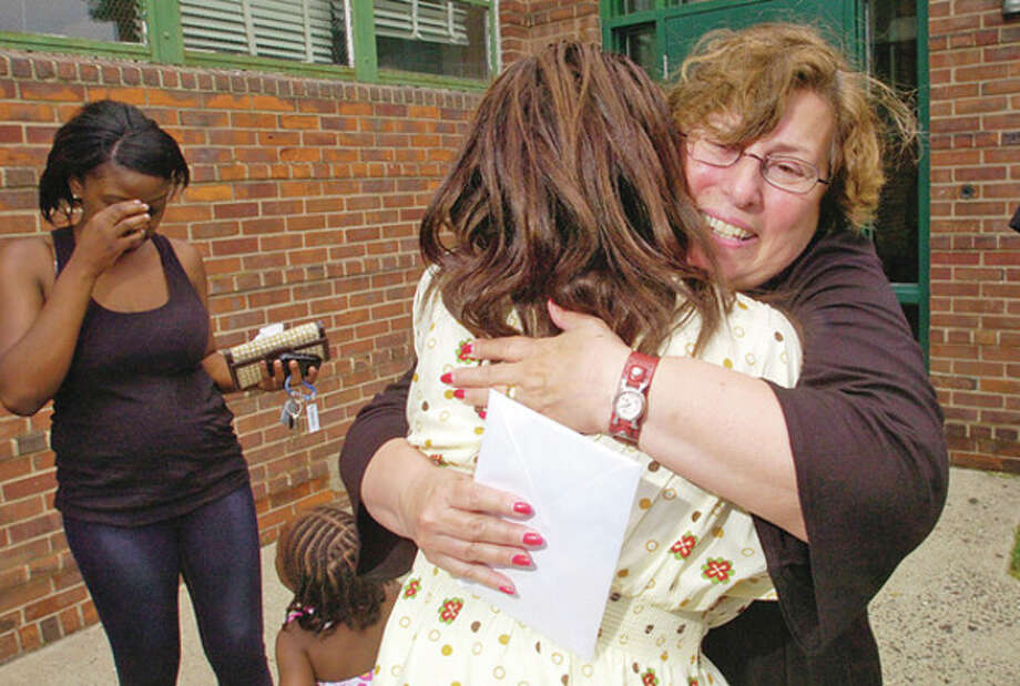 Briggs High School Principal Elaine Lane receives well wishes from former student Courtney Bennett during a retirement party for Lane at the school Friday. / (C)2011, The Hour Newspapers, all rights reserved