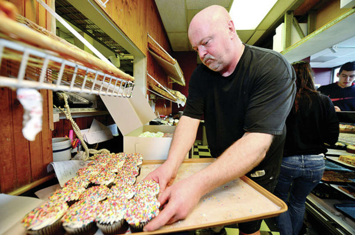 Hour photo / Erik Trautmann Richard Dickenson, owner of Great Cakes, serves customers at his Post Road East location. Great Cakes may be closing its doors in the next few days after a nearly 30-year run due to a lack of business and the discontinued sales of cupcakes to the Westport School system.