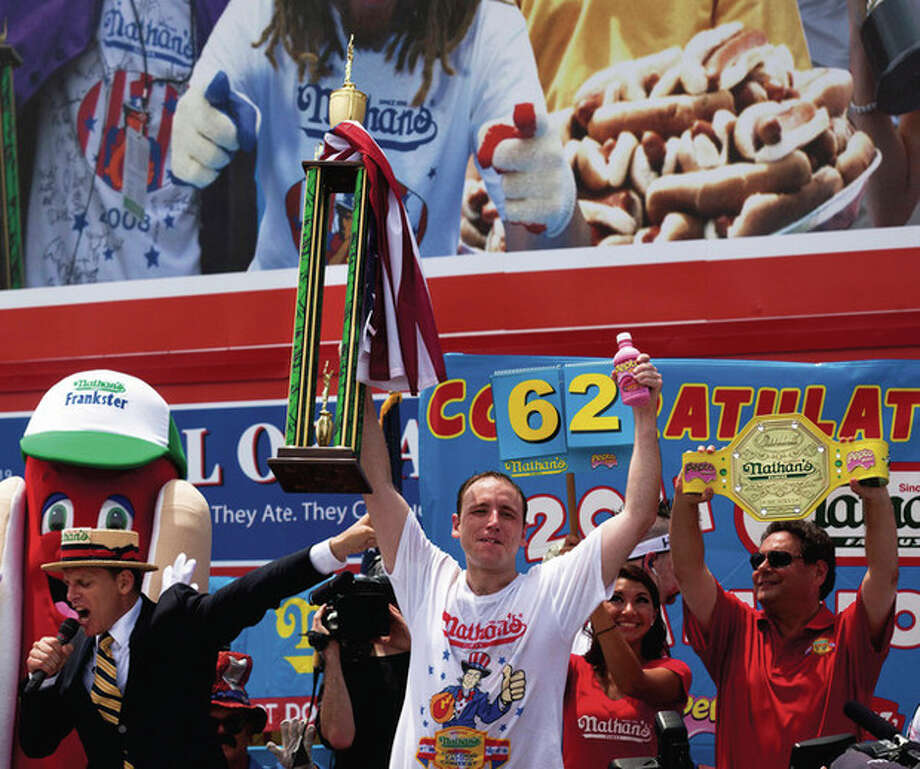 With his trophy in one hand and a bottle of Pepto-Bismol in the other, four-time reigning champion Joey Chestnut, center, accepts his trophy after he wins his fifth NathanÕs Famous Hot Dog Eating World Championship with a total of 62 hot dogs and buns, Monday, July 4, 2011, at Coney Island, in the Brooklyn borough of New York. He was unable to break his world record of 68 hot dogs and buns in 10 minutes. (AP Photo/John Minchillo) / FRE 170537