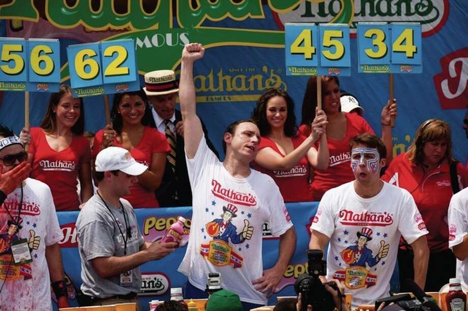 Four-time reigning champion Joey Chestnut, center, raises his arm in victory as he wins his fifth NathanÕs Famous Hot Dog Eating World Championship with a total of 62 hot dogs and buns, Monday, July 4, 2011, at Coney Island, in the Brooklyn borough of New York. (AP Photo/John Minchillo) / FRE 170537