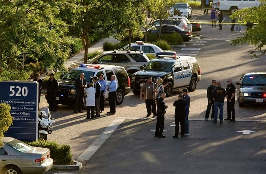 Police and medical personnel stand outside a medical office near Hoag Hospital where shots were fired on Monday, Jan. 28, 2013, in Newport Beach, Calif. Police say a doctor has been shot and killed and a man is in police custody. (AP Photo/The Orange County Register, Leonard Ortiz) / Orange County Register
