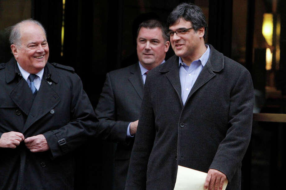 Former CIA officer John Kiriakou, right, and his lawyers Plato Cacheris, left, and John Hundley, leave federal court in Alexandria, Va., Monday, Jan. 23, 2012. In the latest criminal case in the Obama administration's effort to punish leakers, Kiriakou, who helped track down and capture a top terror suspect was charged Monday with disclosing classified secrets about his teammates to the media. (AP Photo/Jacquelyn Martin) / AP