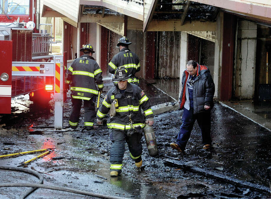 Fire deparment crews work on the aftermath of a fire that worked it's way through a condo complex on Oakdale Avenue in Norwalk on Sunday morning. hour photo/Matthew Vinci