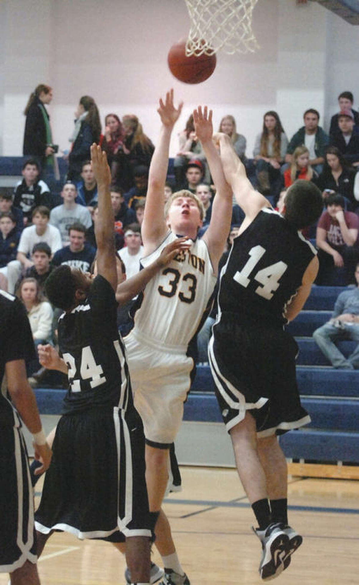 Hour photo/Alex von Kleydorff Weston's # 33 Erik Damnen-Brower stretches to grab a rebound between a pair of Trumbull players during Wednesday night's non-conference clash in Weston. Dammen-Brower and the Trojans grabbed a 70-56 victory.