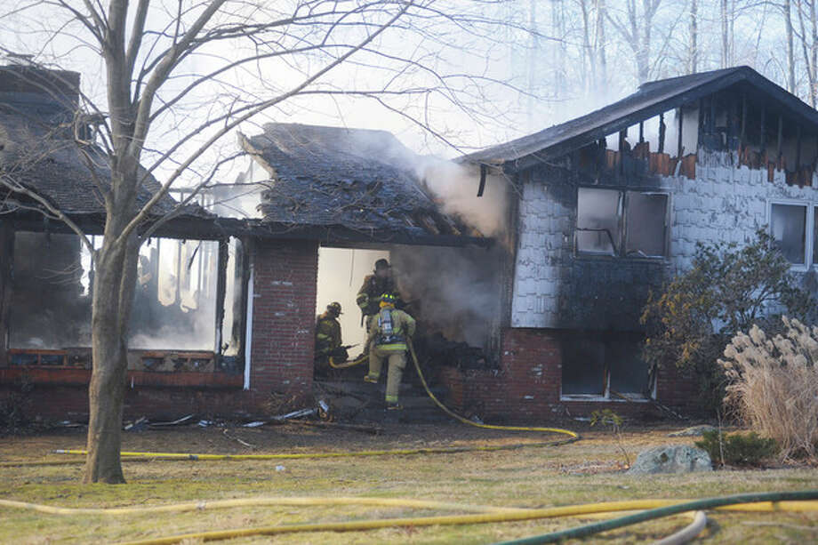 Hour photos / Matthew Vinci Above and below, firefighters battle a fire that destroyed a home at 43 Fawn Lane in New Canaan early Sunday afternoon. / (C)2011, The Hour Newspapers, all rights reserved
