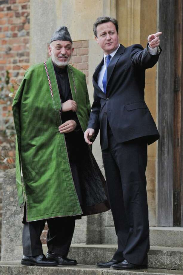 British Prime Minister David Cameron, right, greets President Hamid Karzai of Afghanistan as they meet at the Prime Minister's country residence of Chequers, at Ellesborough west of London, Saturday Jan. 28, 2012. (AP Photo/Carl Court, Pool)