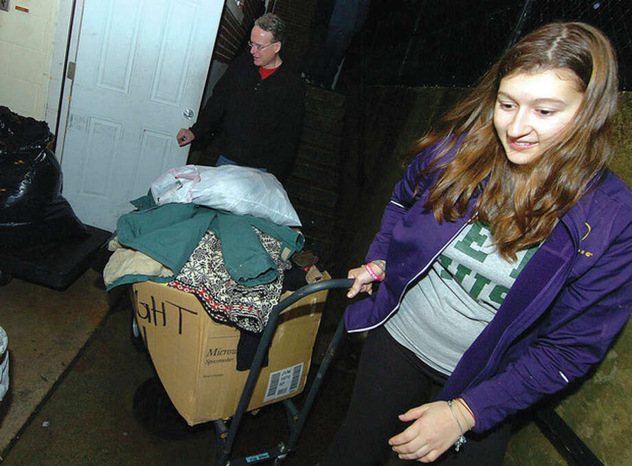 Hour Photo/ Alex von Kleydorff. Megan Carney hauls away filled boxes of clothing for the St Phillip Church Midnight Run. / © 2012 The Hour Newspapers