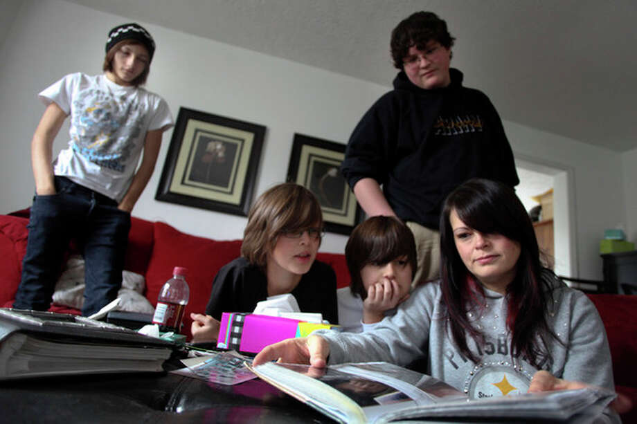 Tina Crouse, right, looks through the family scrapbook in the living room of their Christiansburg, Va. home on Saturday, Dec. 10 2011. From left are family members Dustin Crouse, 16, Tyler Robinette, 11, Peyton Robinette, 9, and Hayden Schack, 15. Officer Deriek W. Crouse was making a traffic stop when police say Ross Truett Ashley, a 22-year-old college student, walked up to his cruiser and shot him. (AP Photo/The Roanoke Times, Matt Gentry) / The Roanoke Times