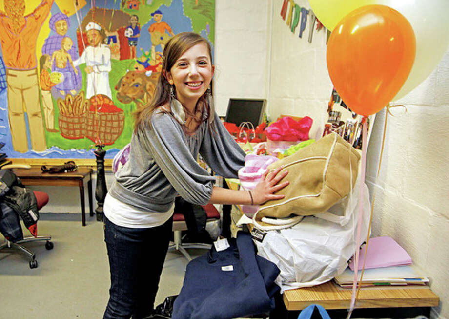 Hour photo / Danielle Robinson Grace Godeski, 12, piles up her birthday gifts at the St. Philip Teen Center in Norwalk. She is donating them to the youth of her church which they will distribute during the Midnight Run Homeless Service Mission in New York City.