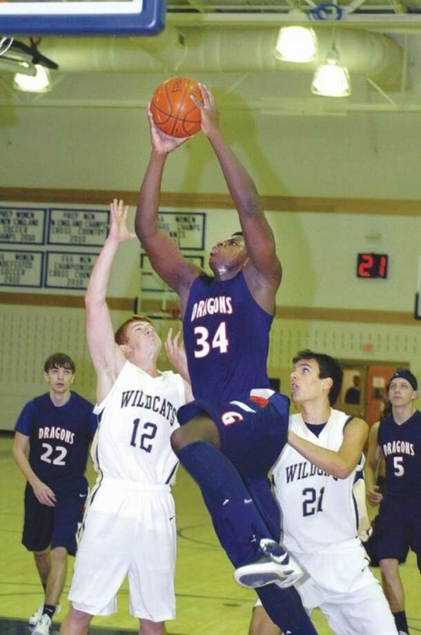 GFA's Sean Obi powers to the hoop between Rye Country Day defenders Sean Grasso (12) and Ienacid Delara during Thursday's game. Hour photo/ Alex von Kleydorff