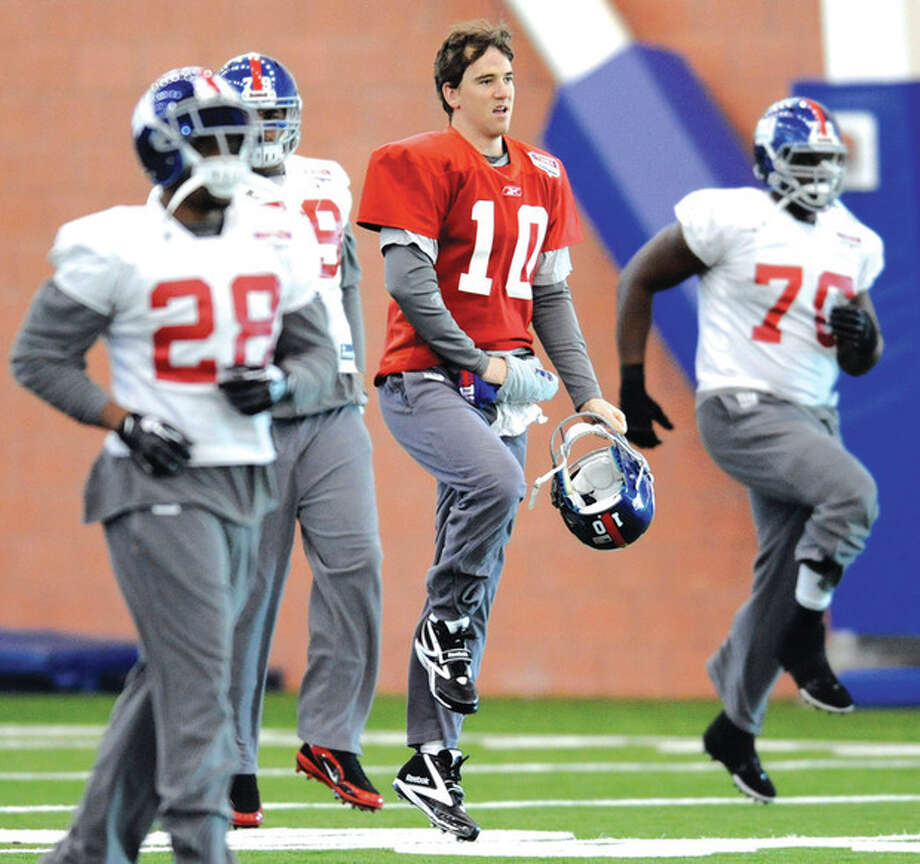 AP photo After missing a day of practice with a stomach bug, quarterback Eli Manning, center, was back at practice Thursday as the New York Giants prepare for Sunday's NFC championship game. / FR51951 AP